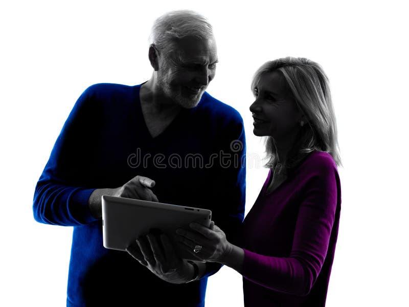 Silhueta digital superior do tablet pc dos pares fotografia de stock