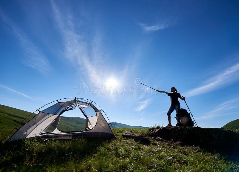 Silhueta do acampamento próximo do montanhista da mulher contra o céu azul na manhã imagens de stock