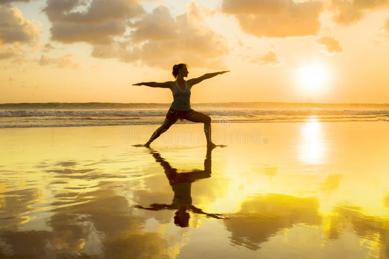 A silhueta do ajuste dos jovens e a aptidão praticando e a ioga da mulher atrativa saudável no por do sol bonito encalham na medi fotos de stock royalty free