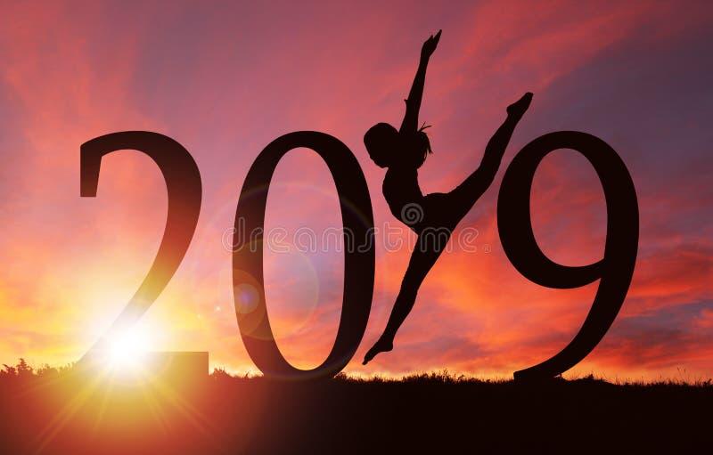 Silhueta do ano 2019 novo da dança da menina no nascer do sol dourado fotografia de stock