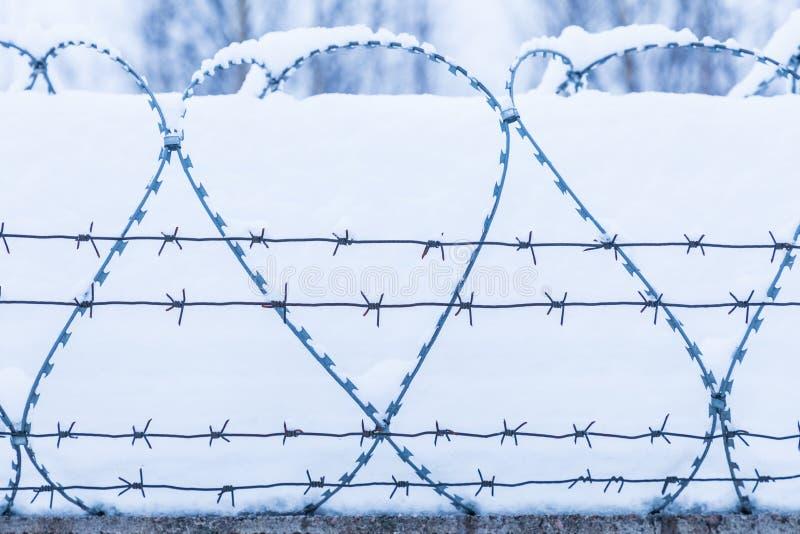 A silhueta do arame farpado no fundo da neve e do céu imagem de stock royalty free