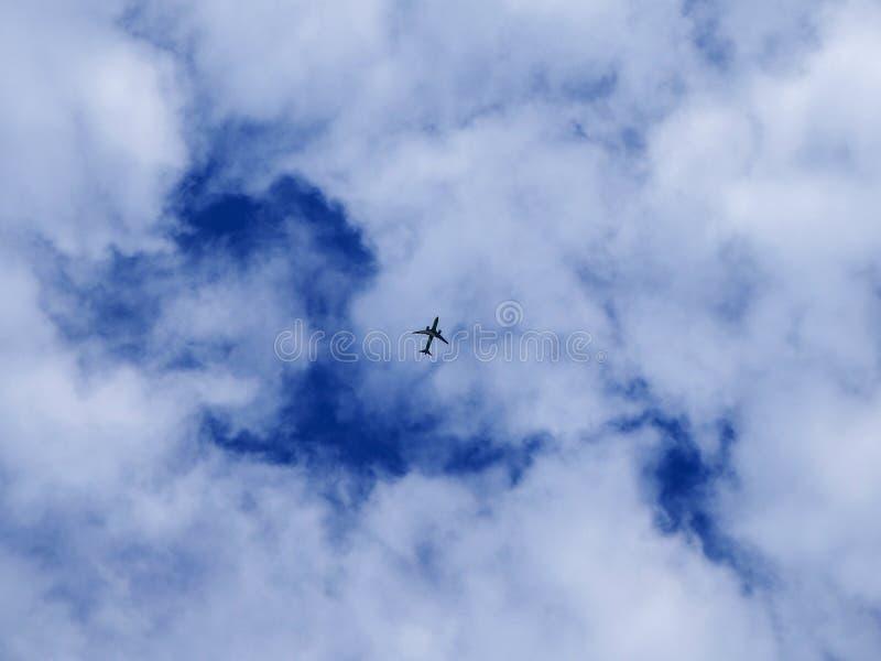 Silhueta do avião em um fundo do céu azul e das nuvens brancas fotos de stock royalty free