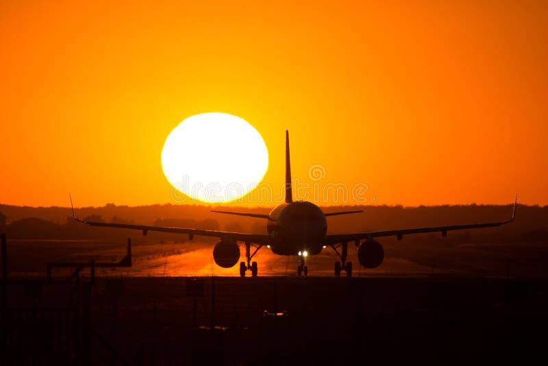 Silhueta do avião no por do sol, após a aterrissagem foto de stock royalty free