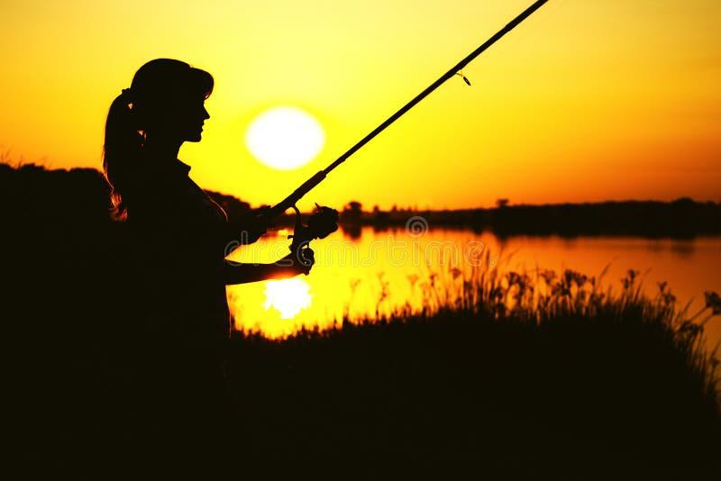 Silhueta do awoman com uma vara de pesca no banco de rio fotografia de stock