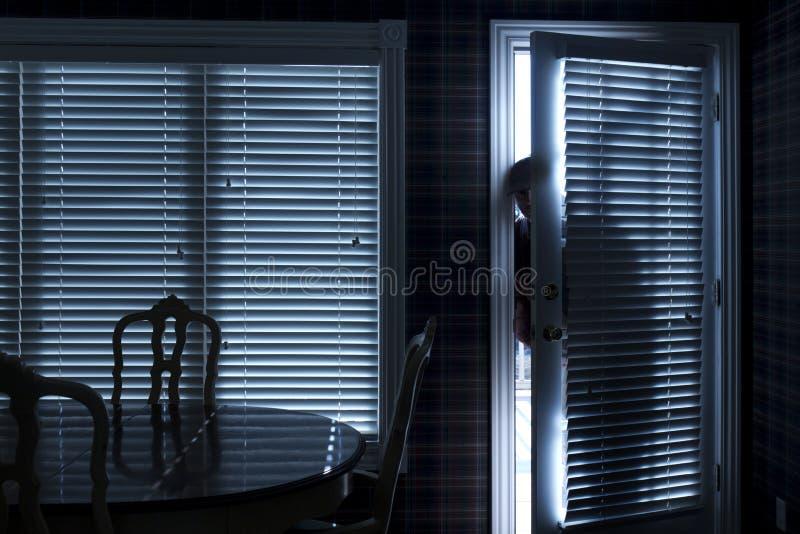 Silhueta do Backdoor de Sneeking Up To do assaltante na noite fotos de stock royalty free
