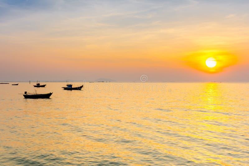 Silhueta do barco da pesca no mar com céu do por do sol imagens de stock