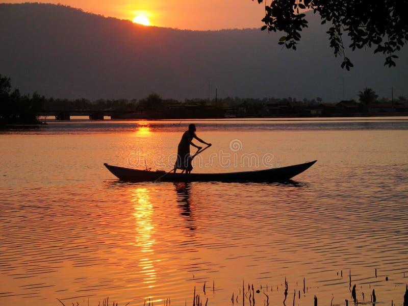 Silhueta do barco de enfileiramento no rio tropical fotografia de stock royalty free