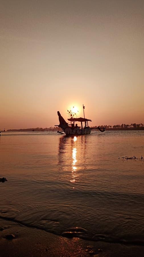 silhueta do barco no crepúsculo quando o sol se ajustar na praia foto de stock