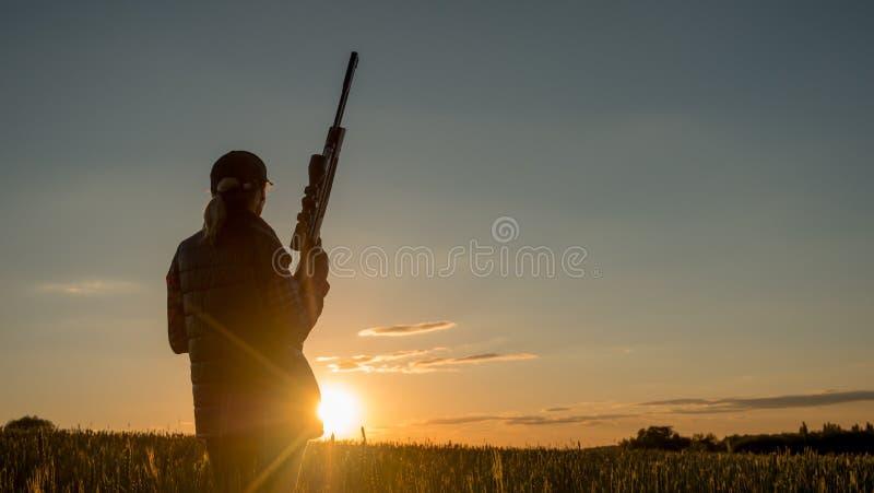 Silhueta do caçador da mulher Está em um lugar pitoresco com uma arma no por do sol Esportes que disparam e que caçam no conceito imagens de stock