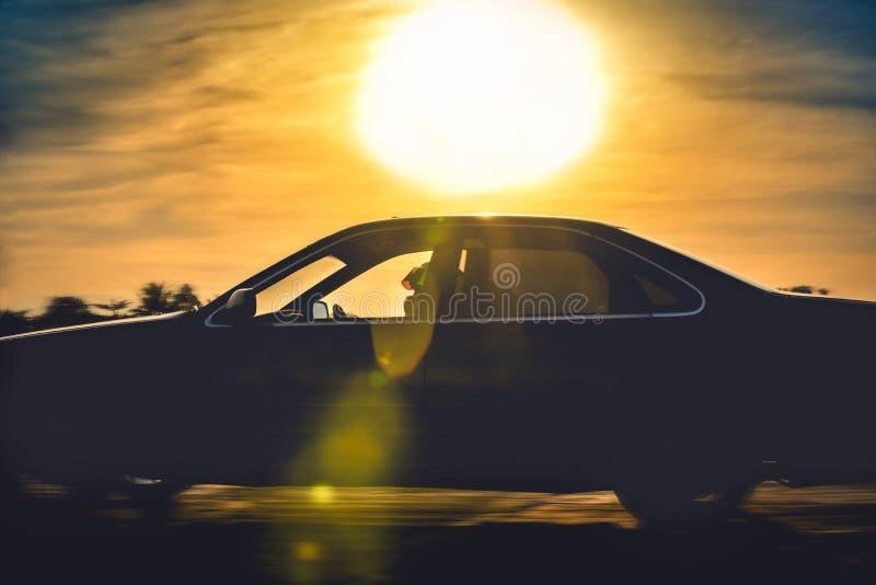 A silhueta do carro move-se com a luz do fundo e a SU foto de stock royalty free