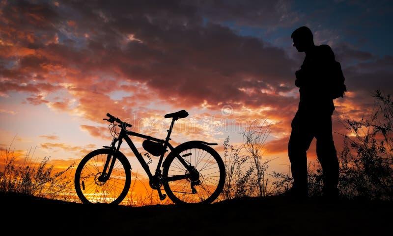 Silhueta do ciclismo da pessoa de esportes no prado no por do sol bonito. Homem novo com c?mera e bicicleta foto de stock royalty free