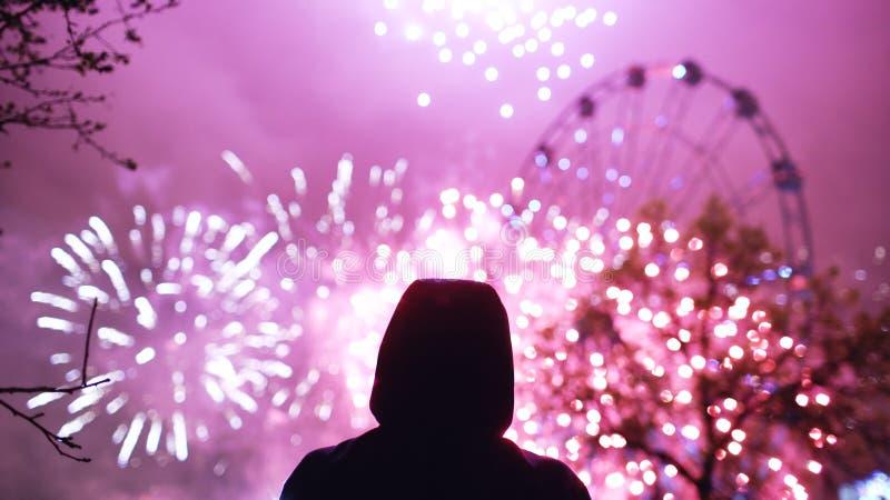 Silhueta do close up de fogos-de-artifício de observação do homem sozinho na celebração do ano novo fora imagem de stock
