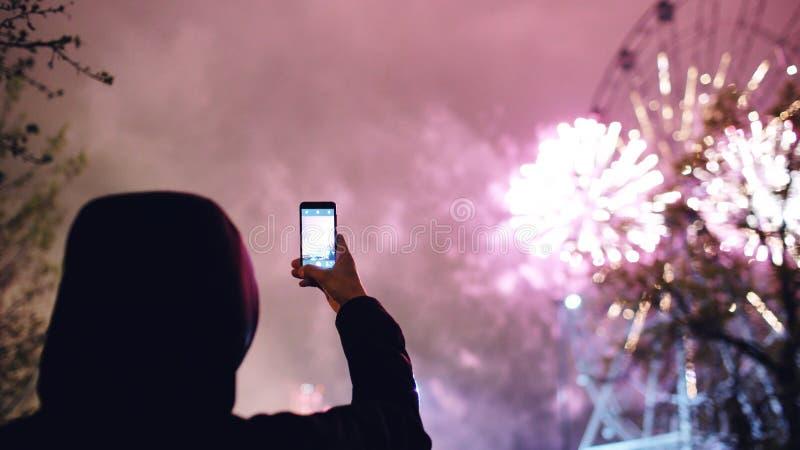 A silhueta do close up do homem que olha e que fotografa fogos-de-artifício explode na câmera do smartphone fora fotografia de stock royalty free