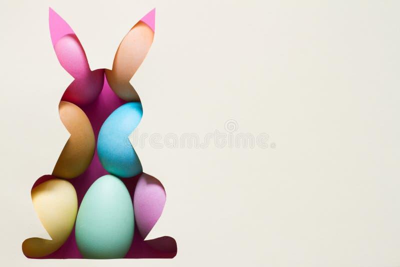 Silhueta do coelho de easter no papel com grama verde e fundo colorido do sumário do ovo imagens de stock