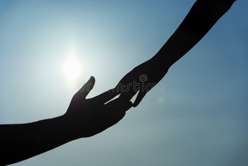 Silhueta do conceito da mão amiga e do dia internacional da paz sustentação Dia internacional da paz Amizade Homem novo em um fun foto de stock