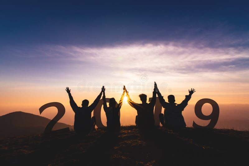 Silhueta 2019 do conceito de Newyear do salto e da mão novos do amigo imagens de stock royalty free