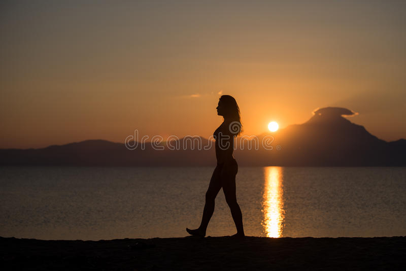 Silhueta do corpo da mulher no nascer do sol na praia fotos de stock royalty free