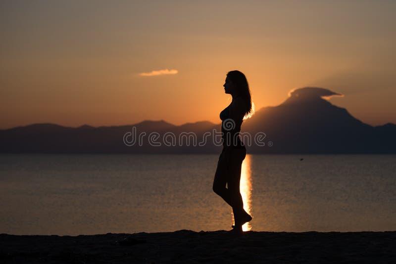 Silhueta do corpo da mulher no nascer do sol na praia imagem de stock