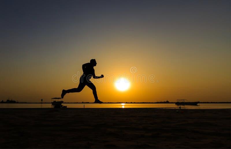 Silhueta do corredor atlético na praia do nascer do sol imagens de stock royalty free