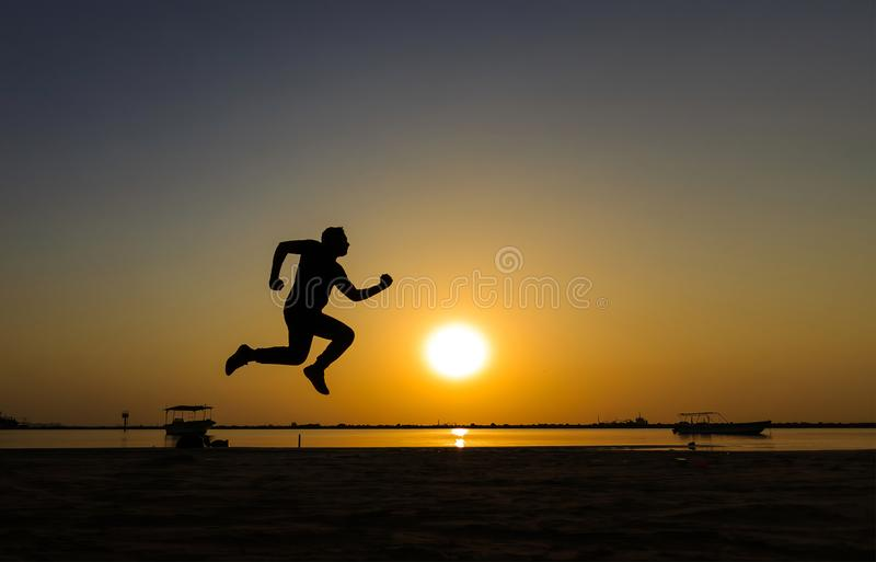 Silhueta do corredor atlético na praia do nascer do sol fotografia de stock