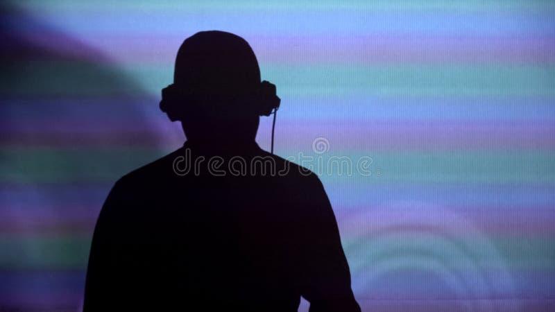 Silhueta do DJ do homem na parede, executando para o partido, dançando à música, opinião da parte traseira imagem de stock royalty free