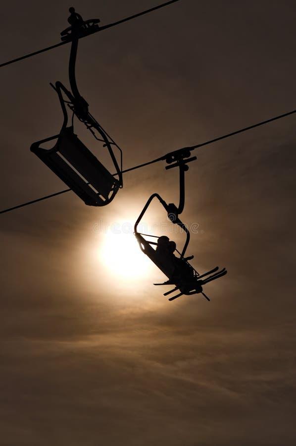 Silhueta do elevador de esqui que toma esquiadores à parte superior fotos de stock royalty free