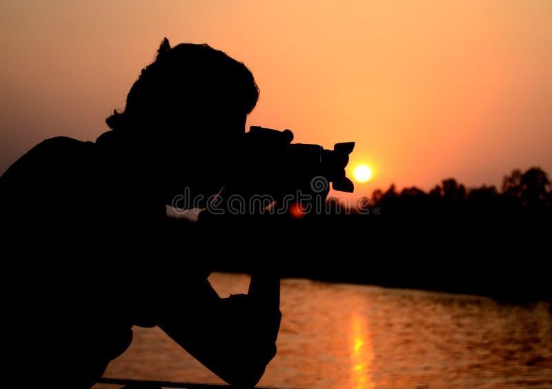 A silhueta do fotógrafo com sol imagens de stock