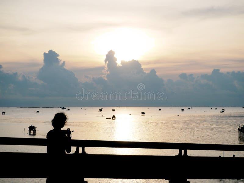 Silhueta do fotógrafo da jovem senhora na ponte sobre o mar fotografia de stock royalty free