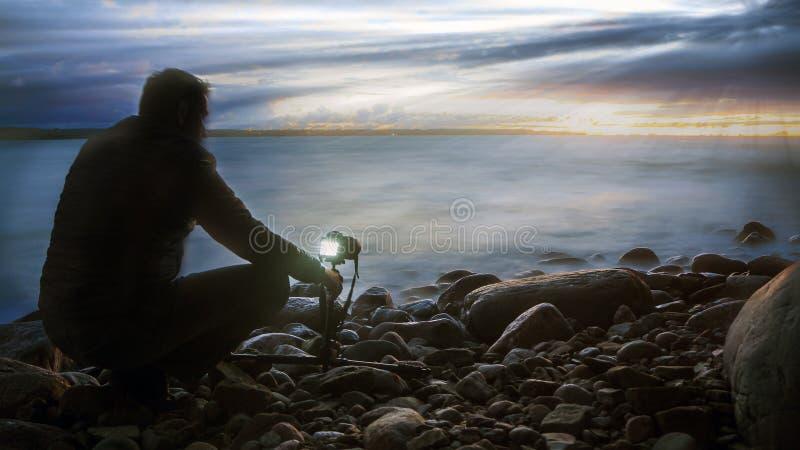 Silhueta do fotógrafo, por do sol fotografia de stock