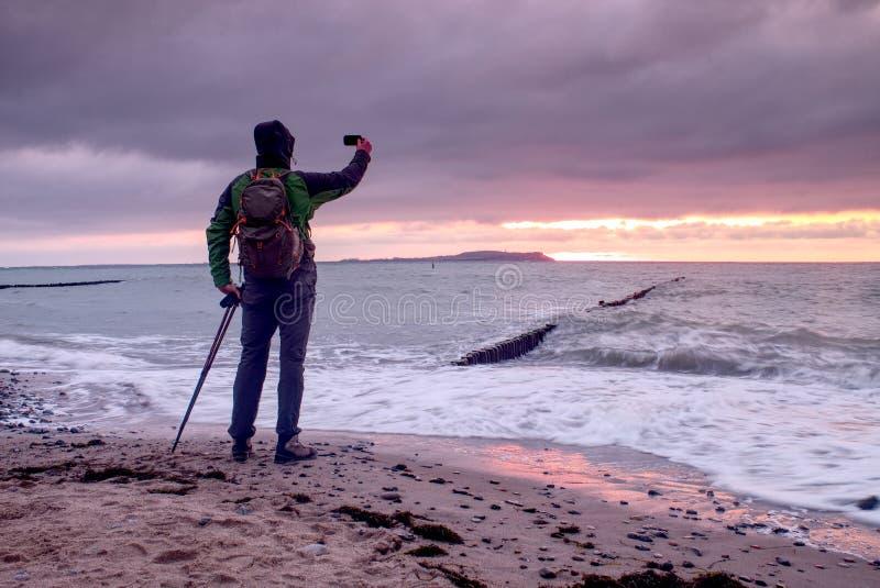 A silhueta do fotógrafo toma a foto da queda no mar com o céu bonito do por do sol fotos de stock royalty free