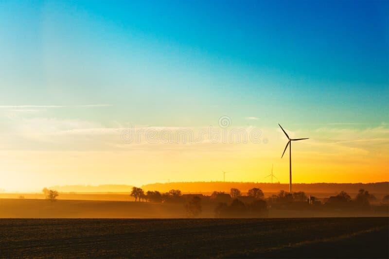 Silhueta do gerador da energia do central elétrica que está na paisagem aberta, nascer do sol de Contrastful fotografia de stock royalty free