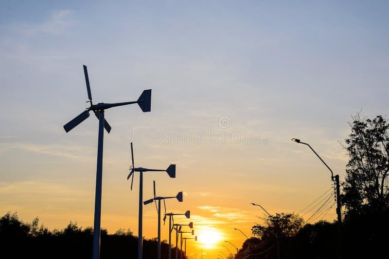 Silhueta do gerador de poder da turbina eólica no por do sol imagens de stock