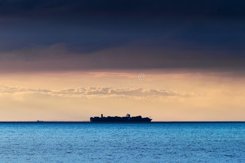 Silhueta do grande mar Báltico do cruzamento do navio de recipiente sob a formação escura dramática da nuvem de nimbostrato imagens de stock royalty free