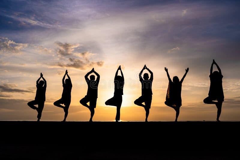 Silhueta do grupo de pessoas que faz a ioga durante o por do sol colorido ou o nascer do sol em uma praia imagem de stock