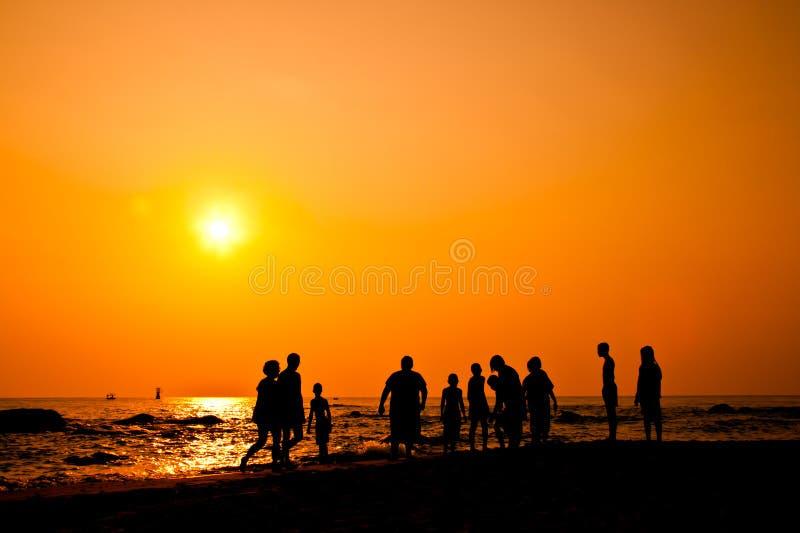 Silhueta do grupo dos miúdos com atividades na praia imagens de stock royalty free