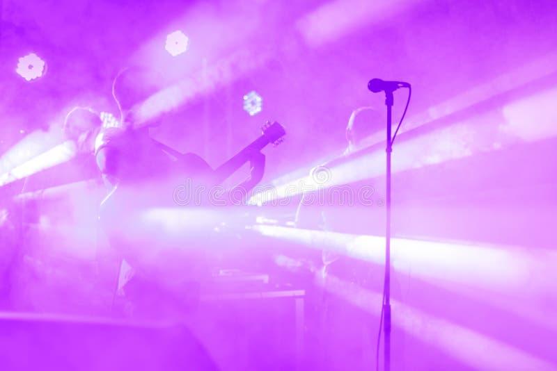 A silhueta do guitarrista executa em uma fase do concerto Fundo musical abstrato Faixa da música com guitarrista Jogo imagens de stock