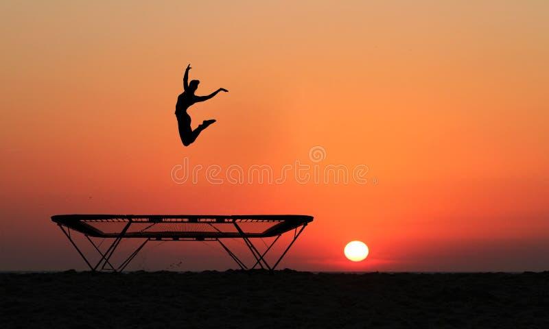 Silhueta do gymnast fêmea que salta no trampolim imagem de stock royalty free