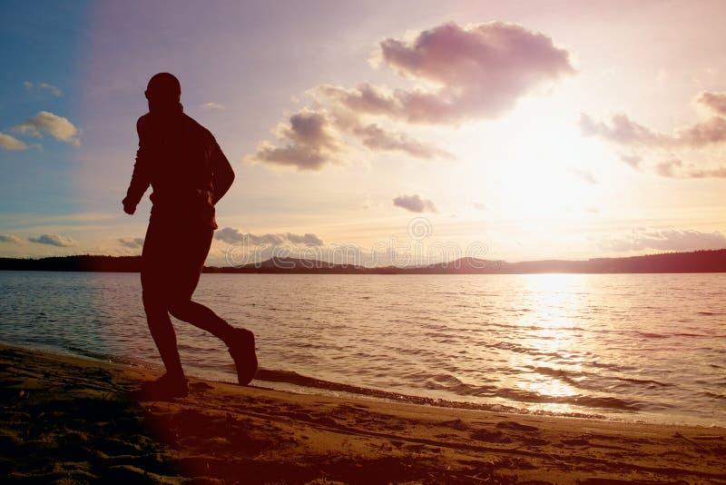 Silhueta do homem ativo do esporte que corre no fundo do céu nebuloso da montanha e do por do sol da água da praia da noite fotos de stock