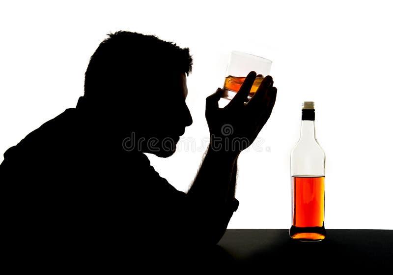 Silhueta do homem bebido alcoólico com vidro do uísque na silhueta do apego de álcool fotografia de stock