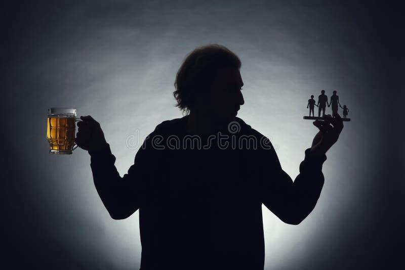 Silhueta do homem com a caneca de cerveja e de figura no fundo escuro Conceito da escolha entre o álcool e a família foto de stock