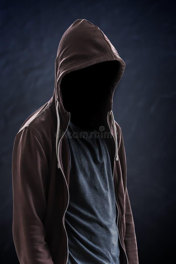 Silhueta do homem com uma capa e da cara no fundo escuro, preto com espaço da cópia foto de stock
