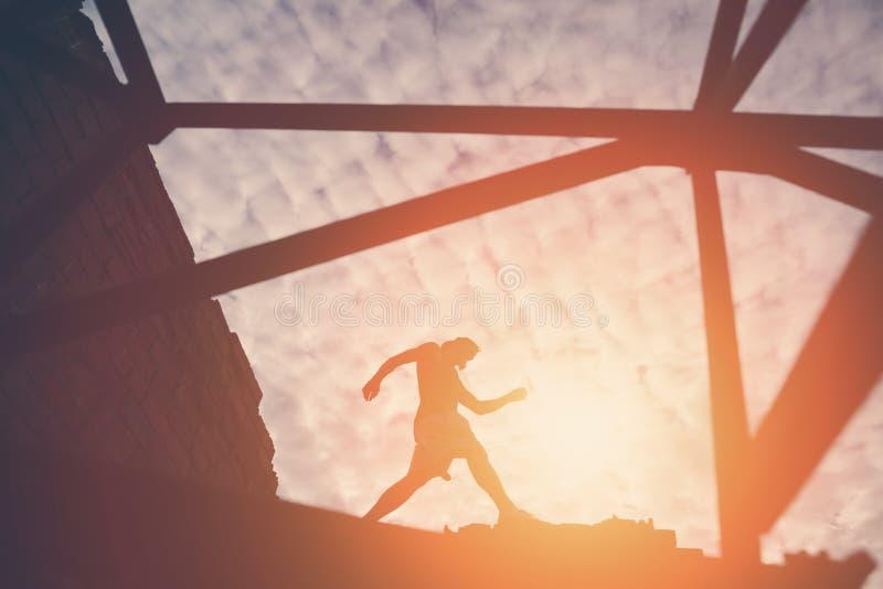 Silhueta do homem corajoso que anda na parte superior das construções no por do sol imagem de stock