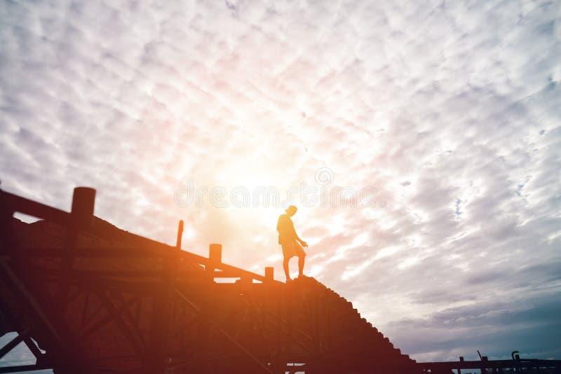 Silhueta do homem corajoso que está na parte superior das construções no por do sol fotografia de stock royalty free