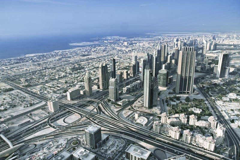 Silhueta do homem de negócio Cowering A skyline de Dubai com a cidade bonita perto dela é ônibus foto de stock