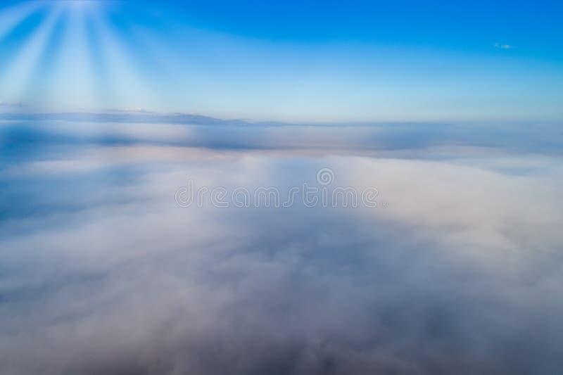 Silhueta do homem de negócio Cowering Voo sobre as nuvens imagem de stock
