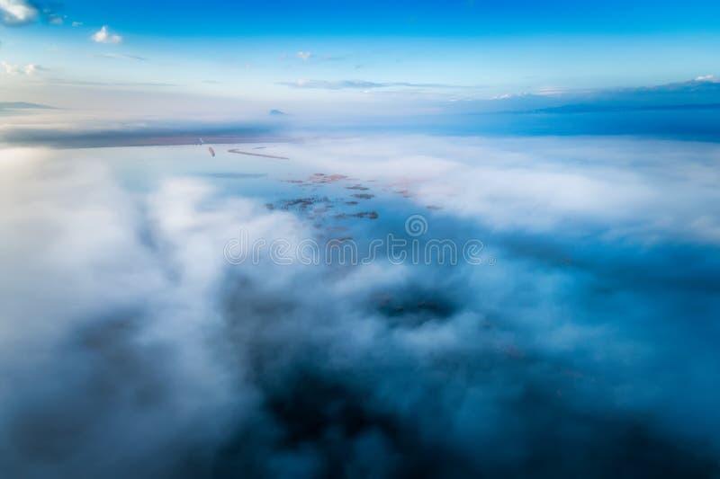 Silhueta do homem de negócio Cowering Voo sobre as nuvens imagens de stock