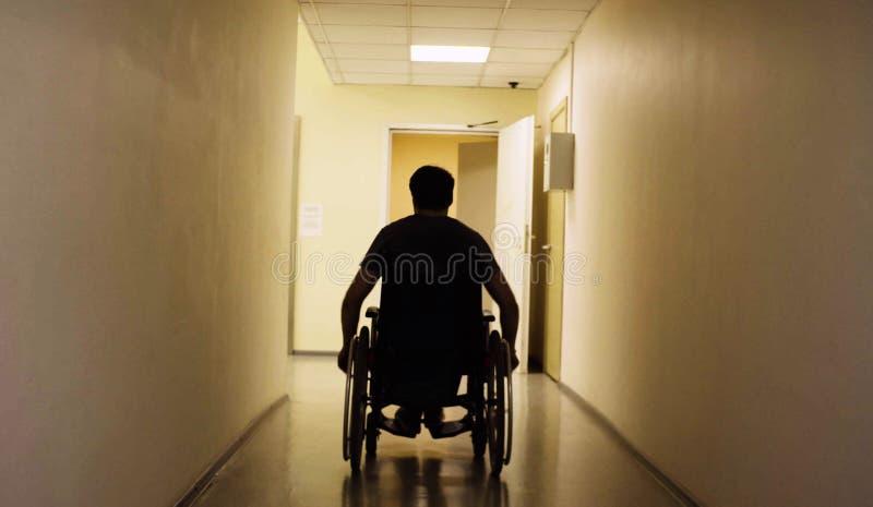 Silhueta do homem deficiente em uma cadeira de rodas no centro de reabilitação fotografia de stock royalty free