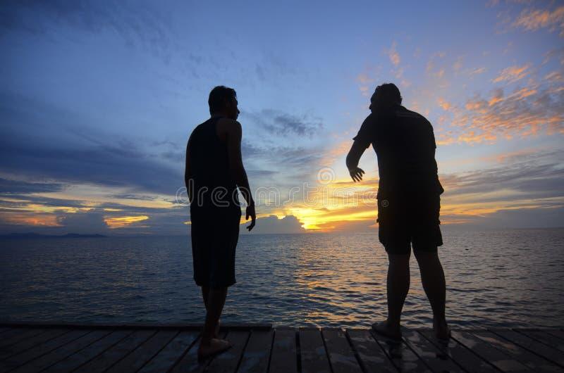 Silhueta do homem dois novo que salta durante o por do sol impressionante imagem de stock royalty free