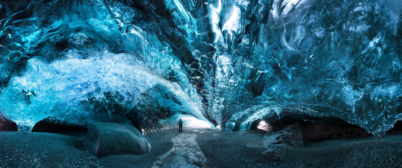 Silhueta do homem na caverna de gelo Caverna de gelo de cristal azul e um rio subterrâneo abaixo da geleira Natureza de surpresa  fotos de stock royalty free