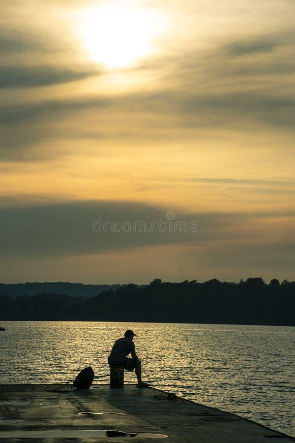 Silhueta do homem na doca de vislumbrar o lago foto de stock